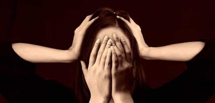 Mujer con estrés por un entorno laboral con riesgos psicosociales