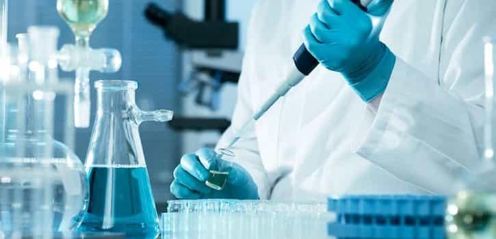 Empleados de un laboratorio trabajando y protegidos frente a los riesgos biológicos