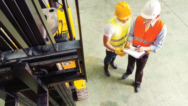 Dos operarios de almacén revisando las condiciones mínimas de seguridad laboral