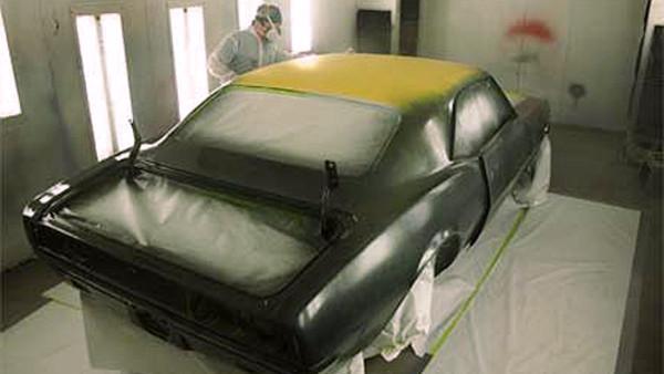 Empleado de taller pintando un coche con las medidas de seguridad reglamentarias