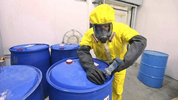 Tranajador con protección para manipular sustancias químicas en una empresa