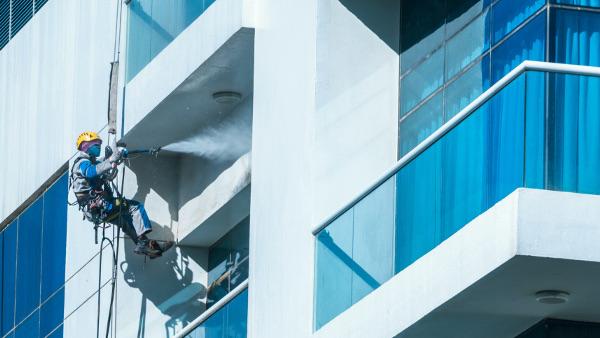 Operario de limpieza con las medidas adecuadas para prevenir riesgos de una caída en altura